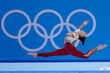 Pauline Schaefer-Betz in a mid-air split wearing the German team red unitard, in front of a banner with Olympic rings.