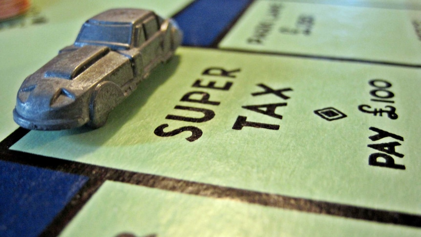 "Close-up of a car figurine on a Monopoly board, landing on the ""Super tax"" square."