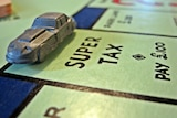 """Close-up of a car figurine on a Monopoly board, landing on the """"Super tax"""" square."""