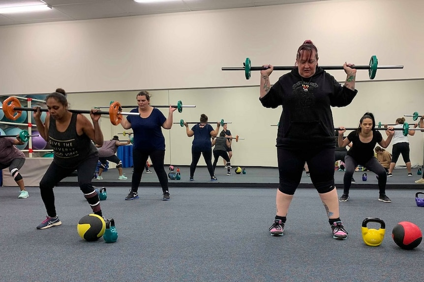 A group of women are lifting metal bars with weights above their heads. The weights are all different colours.