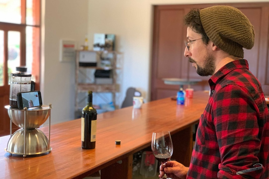 Winemaker Russell Cutting looks at a Zoom meeting on his phone while holding a glass of wine.
