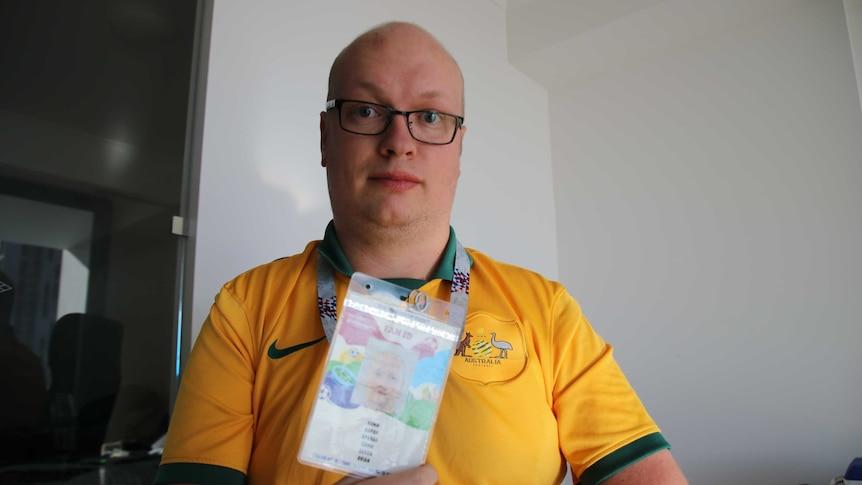 Socceroos fan Aaron Camm holds his Russia 2018 Fan ID