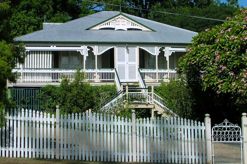 Queenslander house with a white picket fence.