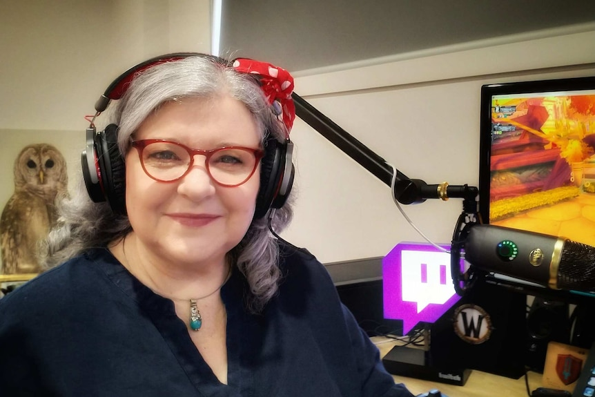 A woman wearing headphones next to a computer.