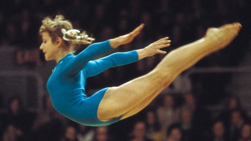A young woman in blue leotard flies through the air with arms outstretched behind her, with blurred crowd behind her.