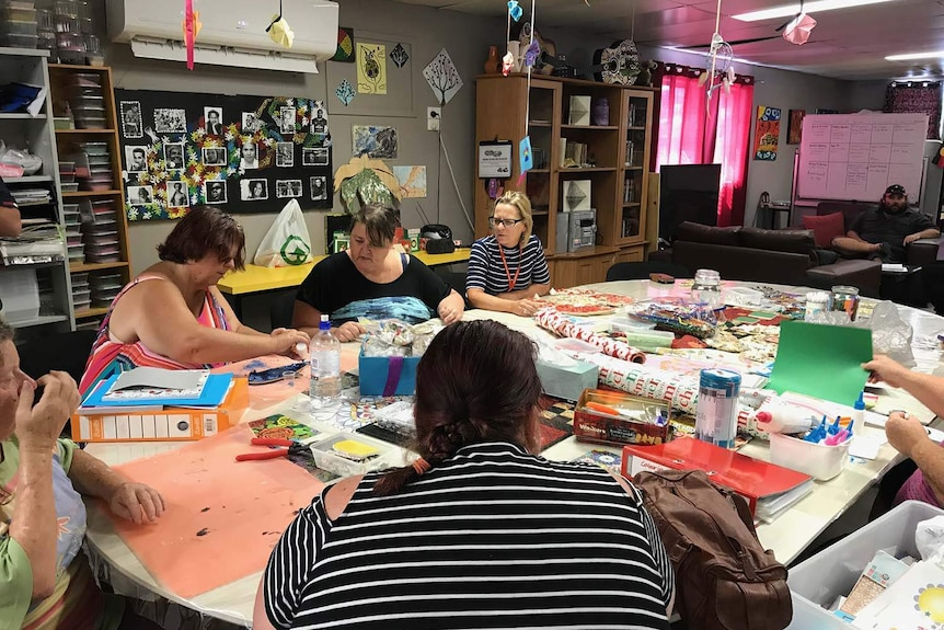 A group of women work on art projects around a large table while a man sits on an arm chair behind.