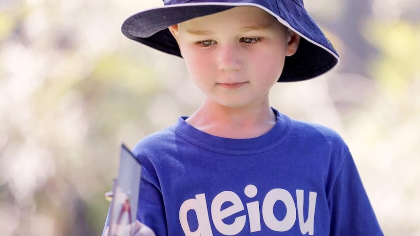 William Wallington stands with a blue hat and AEIOU T-shift on
