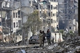 Syrian troops and pro-government stand in the Ansari neighbourhood in East Aleppo