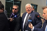 Clive Palmer and his minders outside the Federal Court in Brisbane