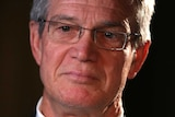 A headshot of Mike Nahan against a black background.