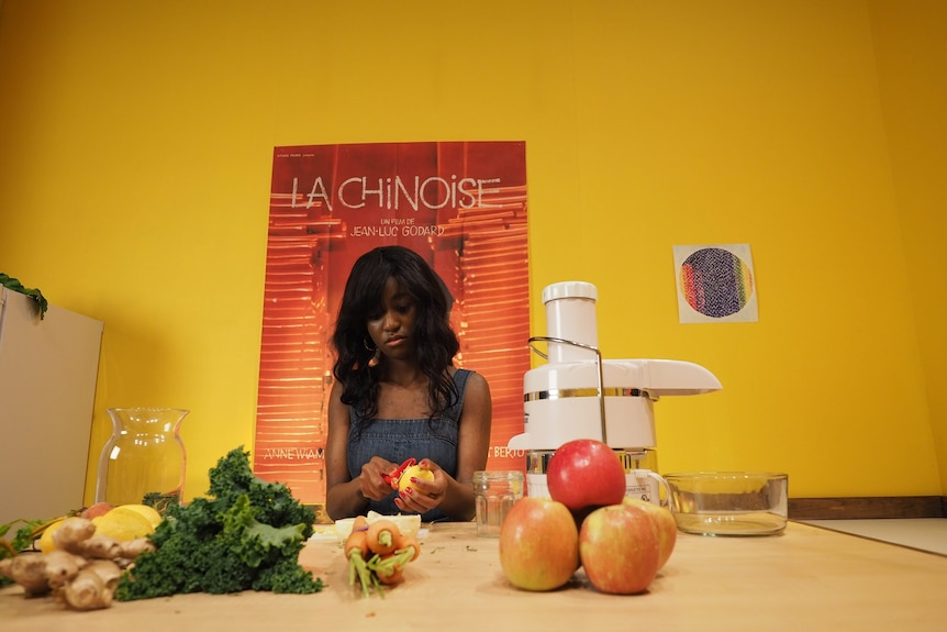 Young Black woman sits at table in bright yellow room cutting fruit, with poster of Godard's film La Chinoise behind her.