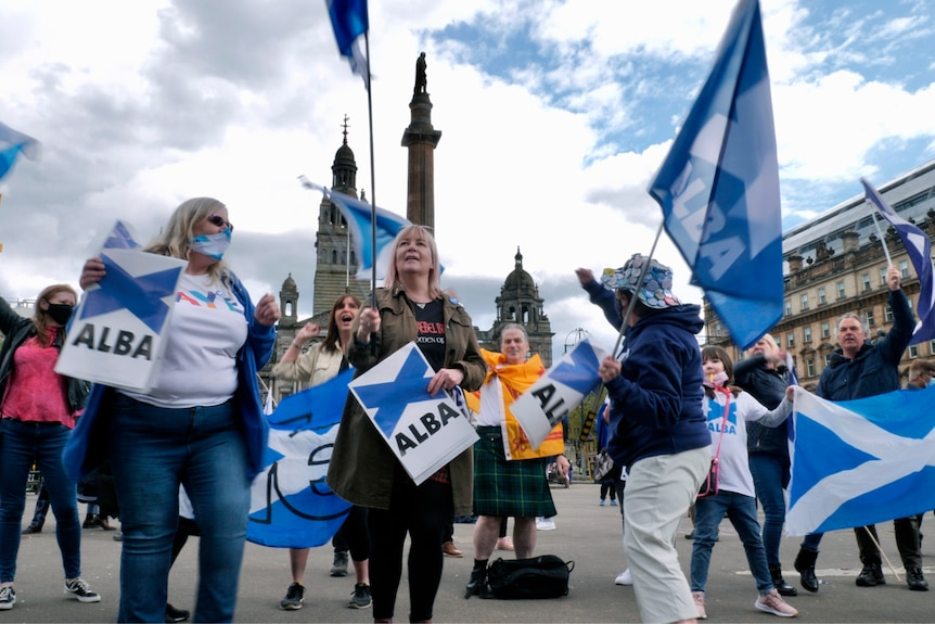 A group of women waving Scottish flags