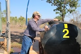 A man fills up a large water container