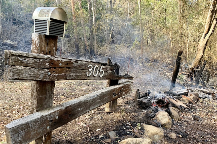 A burnt out letterbox and bushland.