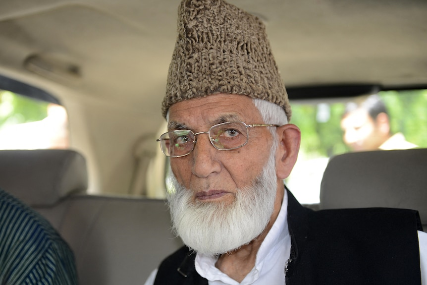 A picture of a man with a white beard and tan knitted hat and glasses