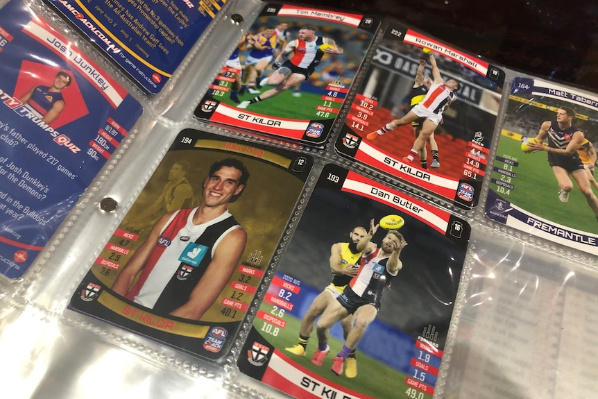 Pages of a plastic folder hold photos of AFL players from the Bulldogs, St Kilda and Fremantle.