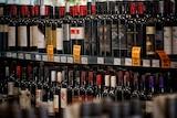Bottles of wine on a shelf in a bottle shop.
