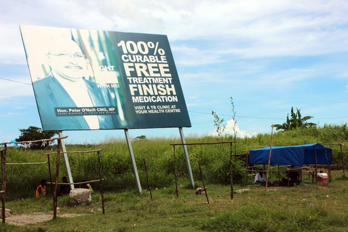 A makeshift shelter next to a TB billboard featuring the Prime Minister, Peter O'Neill.