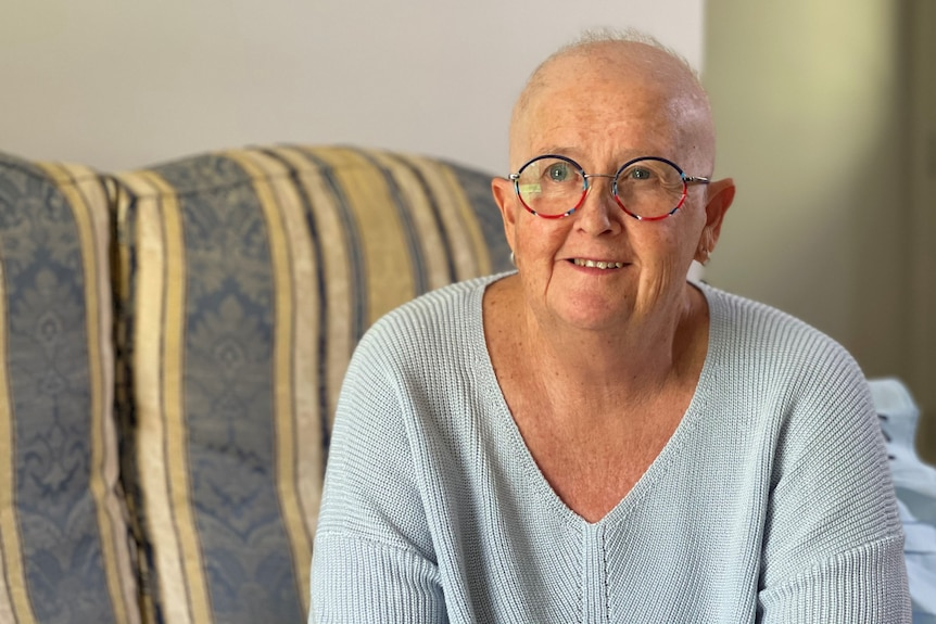 Therese McLean with bald head and wearing glasses