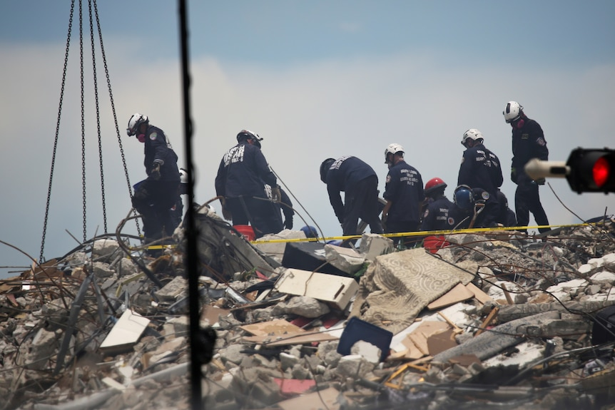 Eight unifiormed resuce workers in hard hats scan the rubble and debris left behind by a collapsed building.