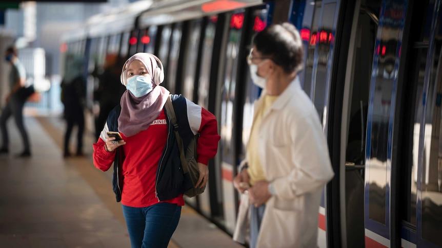 A woman wearing a hijab, headphones, face mask and a man wearing a mask come out of public public transport.