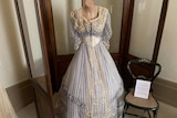 An 1880's  wedding gown made of striped blue and cream silk.