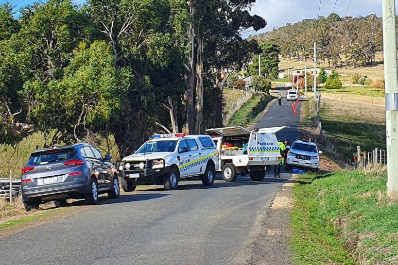 Police cars at the scene of a crash on a country road