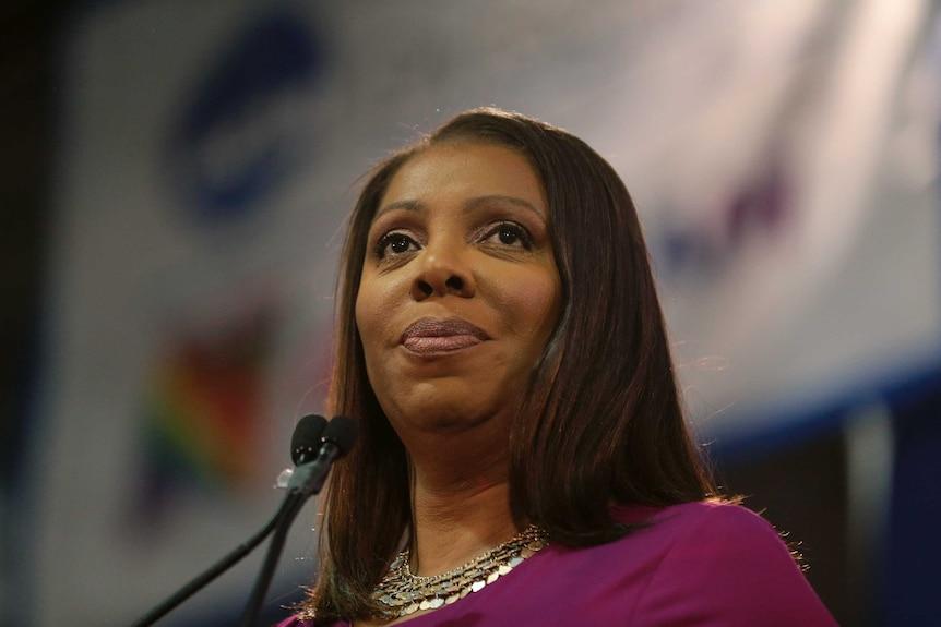 O femeie afro-americană a fotografiat de aproape pe un podium purtând o cămașă mov.