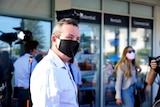 Mark McGowan wearing a black face mask and shirt with no tie, with a photographer in the background.