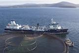 Large salmon processing ship next to fish farming pens.