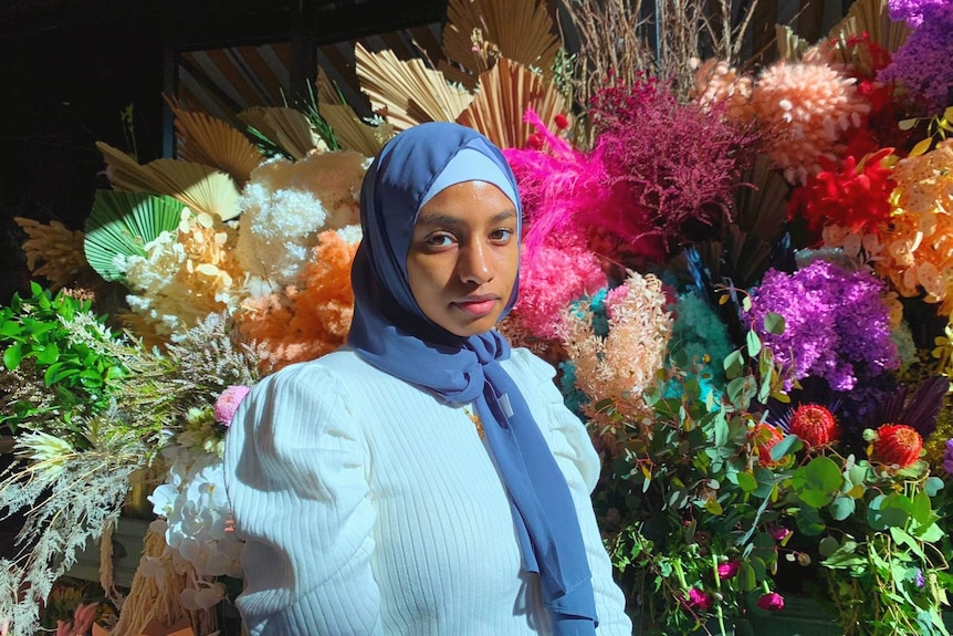 A woman wearing the hijab standing in front of a floral background.