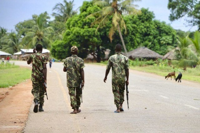 Three African soldiers walk down the middle of a quiet street in tropical setting.