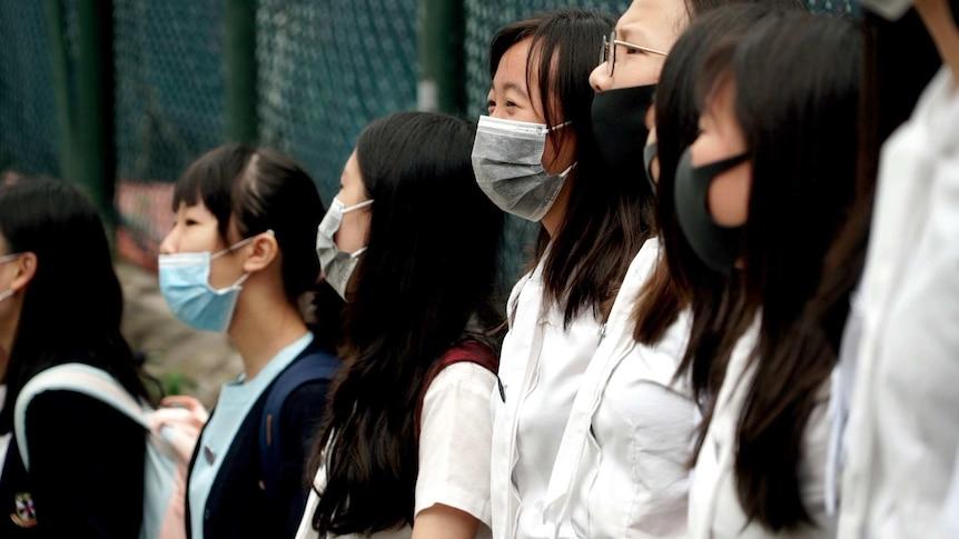 A couple of schoolgirls wear black masks, standing shoulder by shoulder.