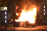 A car burns in the dark next to a roundabout road sign.