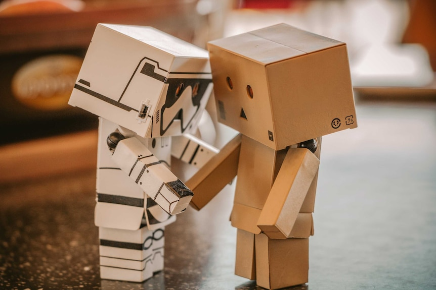 Two robot boxes shaking hands.