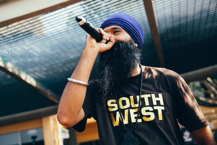 L-FRESH rapping on stage with a microphone in hand, wearing tee-shirt with 'South West' on it.