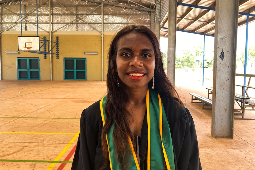 Jazzy Dummo, a student at the college, smiles into the camera. She is standing outside, next to a basketball court.