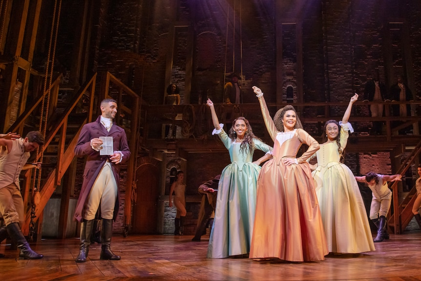 The three Schuyler sisters in 18th century dresses to one side of stage, with Aaron Burr to other side.
