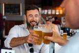smiling man holds up pint of lager in pub