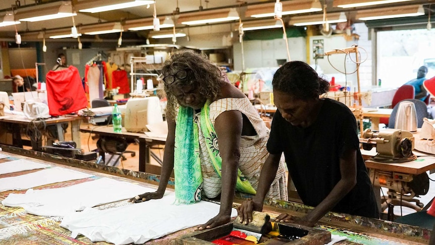 Two women stand at a table in a clothing print shop working on tshirt prints