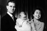 Prince Philip cradles a baby Prince Charles, with Queen Elizabeth II playing with his hand.