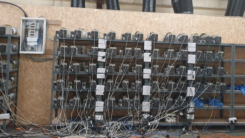 Dozens of computer units sit on shelves among power cables