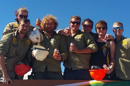 Group shot of members of the WASM Wombats team, holding hard hats and beer cans.