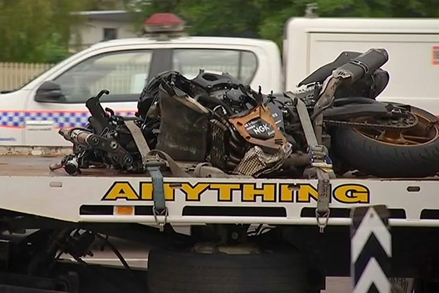 A mangled motorcycle on the back of a flat bed tow truck