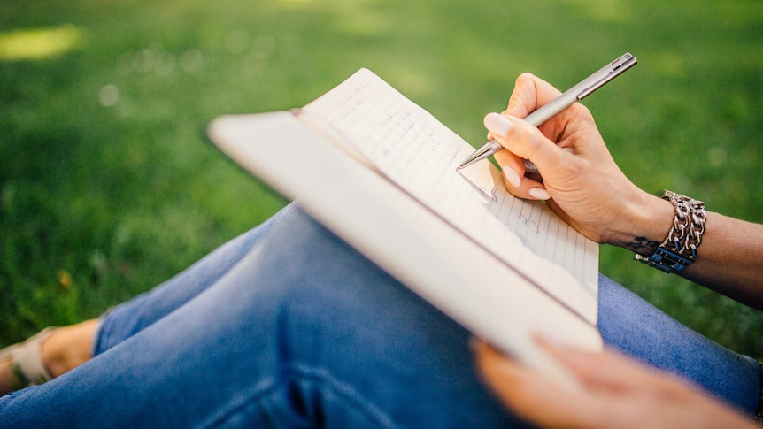 Close-up of woman writing a note in the grass for a story about writing letter to have tough conversations with your partner.
