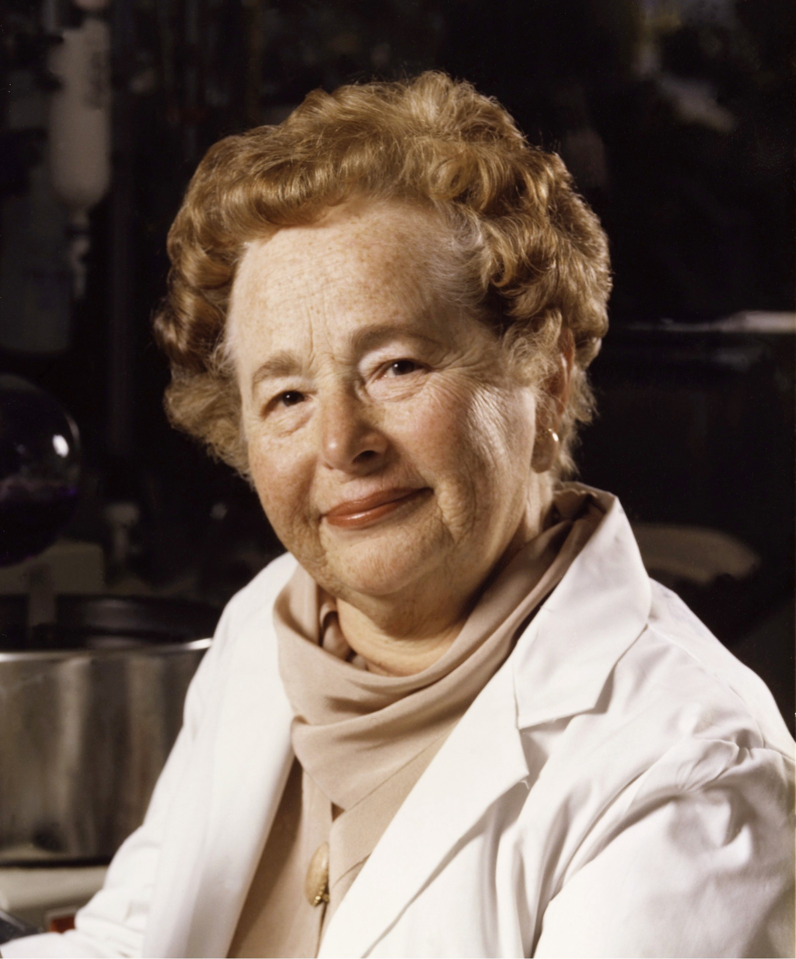 Older woman with short perm hair and white lab coat