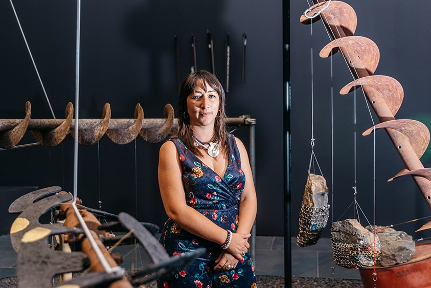 A woman with long dark hair, shell necklace and blue playsuit stands among sculptures made large rust coloured drill augers.