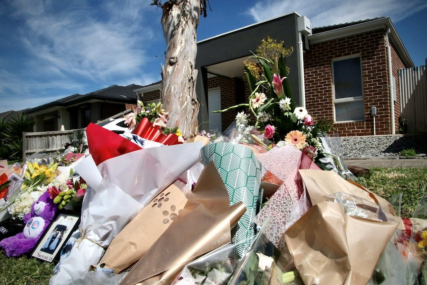 Floral tributes lay by a tree in front of a suburban house.