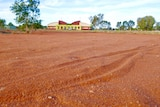 A red sandy area with a building in the background.
