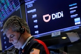 """A stock trader with a headset looks down into a bright screen as a monitor behind him displays the """"D"""" logo of company DiDi."""